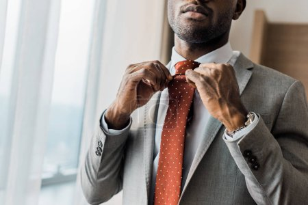 cropped view of african american businessman adjusting red tie