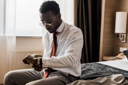 Photo for Young african american businessman looking at wristwatch while sitting on bed in hotel room - Royalty Free Image