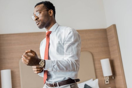 handsome african american businessman wearing wristwatch in hotel room