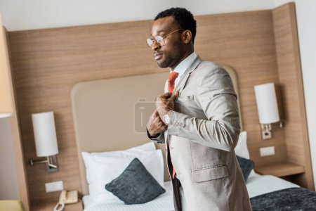 executive african american businessman wearing gray jacket in hotel room
