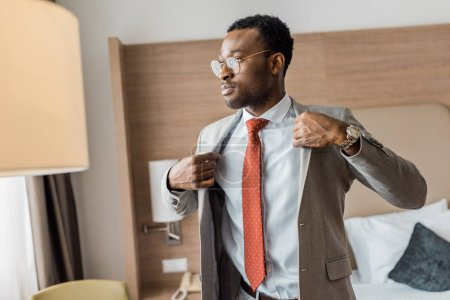 african american businessman wearing gray jacket in hotel room