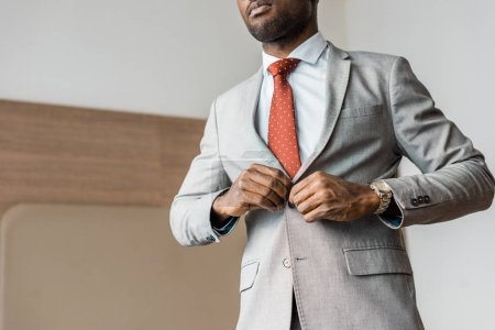 cropped view of african american businessman buttoning gray jacket