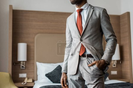 Photo for Cropped view of businessman in gray suit and red tie standing in hotel room - Royalty Free Image
