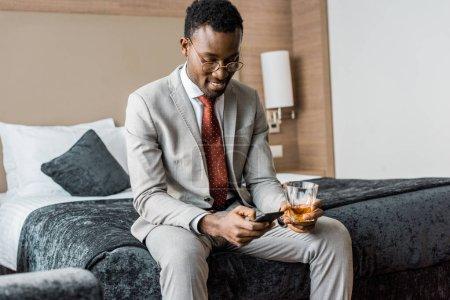 Foto de Sonriente hombre de negocios afroamericano con Copa de coñac con smartphone sentado en la cama en el hotel - Imagen libre de derechos