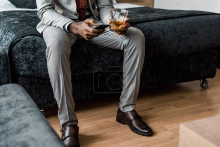 cropped view of african american businessman with glass of whiskey using smartphone in hotel room