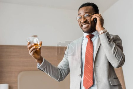 successful smiling african american businessman holding glass of whiskey and talking on smartphone in hotel