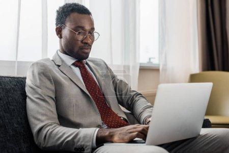 Foto de Guapo hombre de negocios afroamericano utilizando la computadora portátil en la habitación del hotel - Imagen libre de derechos