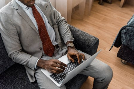 Photo for Cropped view of african american businessman typing on laptop in hotel room - Royalty Free Image
