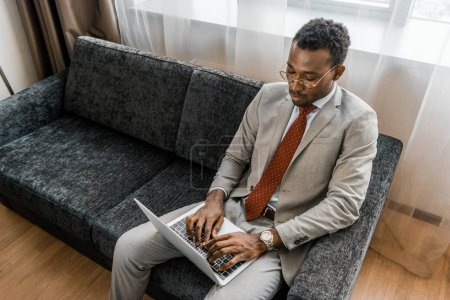 Photo for Elegant african american businessman using laptop in hotel room - Royalty Free Image