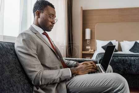 african american businessman working on laptop in hotel room