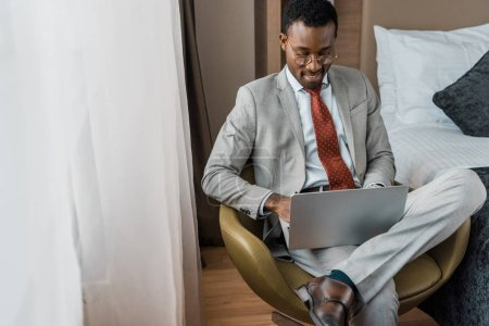 Photo for Handsome smiling african american businessman working on laptop in hotel room - Royalty Free Image