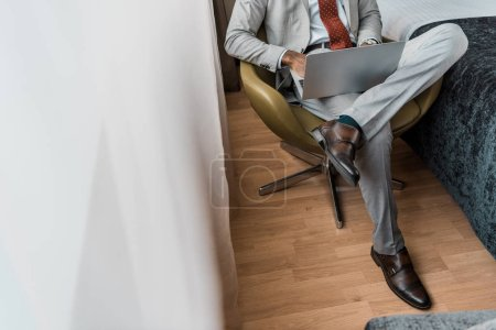 Photo for Cropped view of elegant businessman using laptop in hotel room - Royalty Free Image