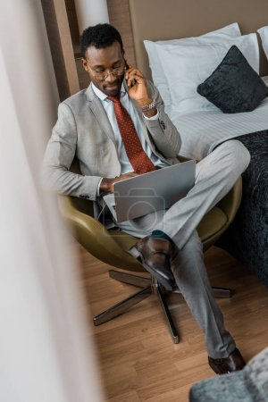 Photo for Handsome african american businessman talking on smartphone and using laptop in hotel room - Royalty Free Image