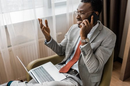 smiling african american businessman gesturing, talking on smartphone and using laptop in hotel room