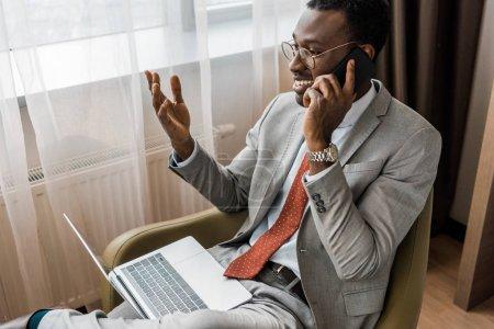 homme d'affaires africain-américain souriant gestuelle, parler sur smartphone et utilisez l'ordinateur portable dans la chambre d'hôtel