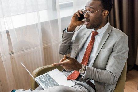 Foto de Próspero hombre de negocios afroamericano hablando en smartphone y apuntando a laptop - Imagen libre de derechos