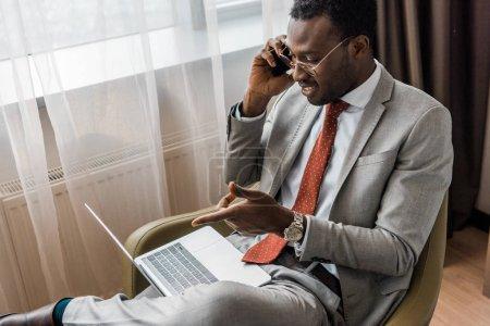 Photo pour Bel homme d'affaires afro-américain souriant parlant sur smartphone et pointant vers un ordinateur portable dans la chambre d'hôtel - image libre de droit