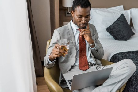 thoughtful african american businessman with glass of cognac looking at laptop in hotel room