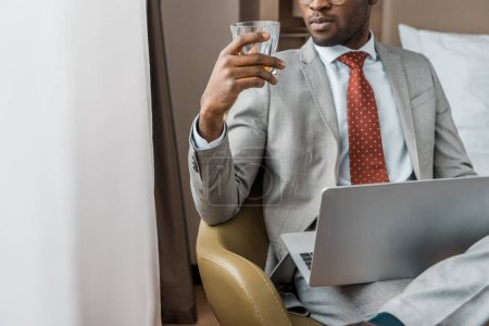 cropped view of african american businessman with laptop looking at glass of alcohol drink in hotel