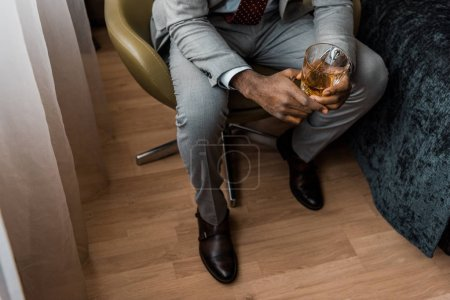 cropped view of african american man holding glass of whiskey