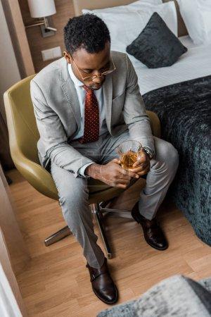depressed african american man holding glass of whiskey in hotel room