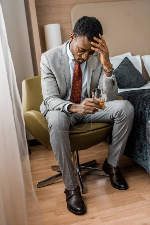 frustrated african american man holding glass of cognac in hotel room
