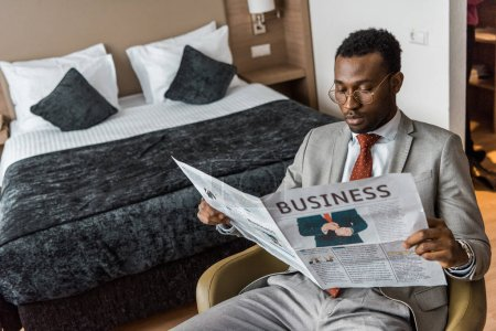 Photo for Serious african american man in suit reading business newspaper in hotel room - Royalty Free Image