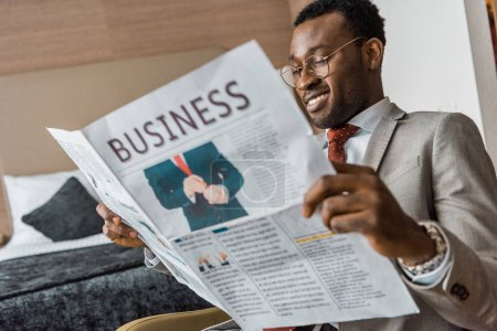 Photo for Smiling african american businessman in suit reading business newspaper in hotel room - Royalty Free Image