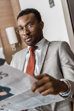 african american businessman in suit holding newspaper and looking at camera