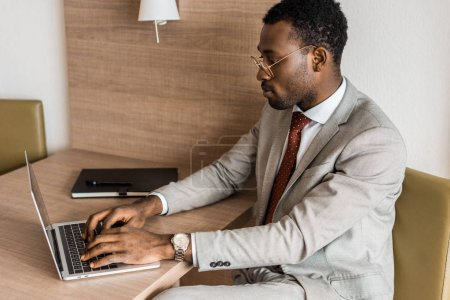 Photo for Concentrated african american businessman typing on laptop in hotel room - Royalty Free Image