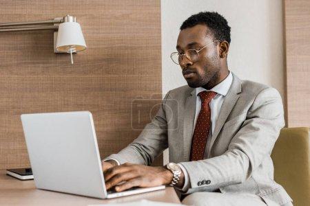 concentré d'africain-américain homme d'affaires, dactylographie sur ordinateur portable dans la chambre d'hôtel