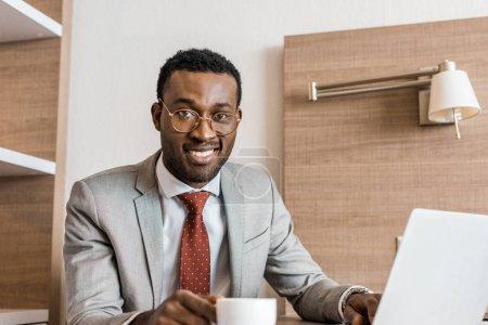 Photo pour Homme d'affaires afro-américain souriant avec ordinateur portable pendant la pause café dans la chambre d'hôtel - image libre de droit