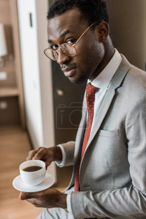 Photo for Handsome african american businessman holding coffee cup in hotel room - Royalty Free Image