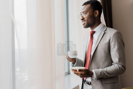 handsome businessman in suit holding cup of coffee near window in hotel room