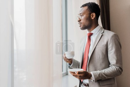 african american businessman holding cup of coffee near window in hotel room
