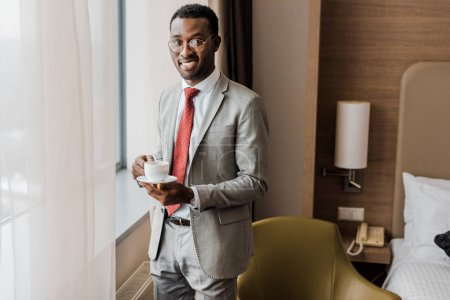 Photo for Cheerful african american businessman holding coffee cup in hotel room - Royalty Free Image