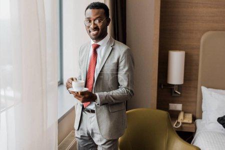 Photo pour Joyeux homme d'affaires afro-américain tenant tasse de café dans la chambre d'hôtel - image libre de droit