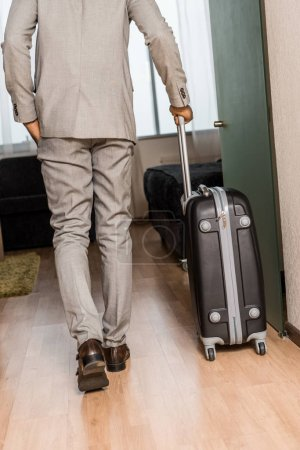 back view of businessman in grey suit with travel bag coming into hotel room