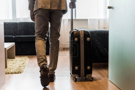 cropped view of businessman in suit with baggage coming into hotel room