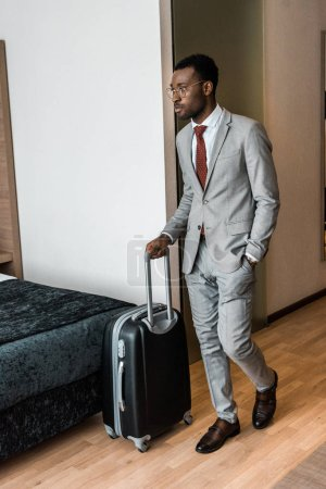 african american businessman with travel bag coming into hotel room