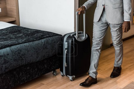 cropped view of businessman with travel bag in hotel room
