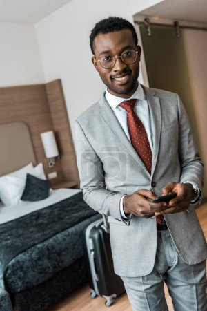smiling african american businessman using smartphone in hotel room