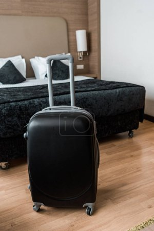 Photo for Black travel bag in hotel room with bed - Royalty Free Image