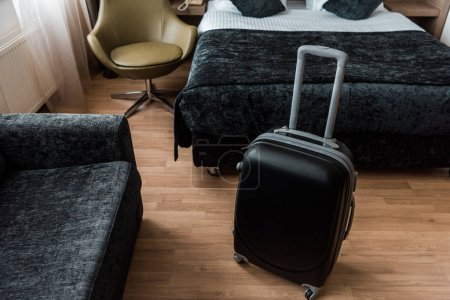 Photo for Black suitcase for travel in hotel room with bed and armchair - Royalty Free Image