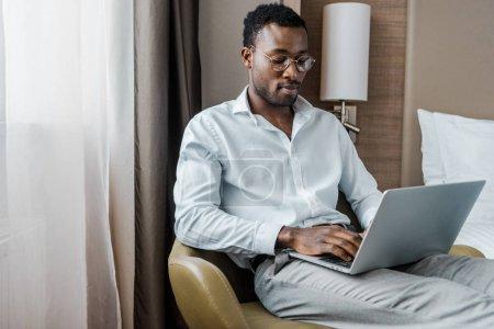 jeune homme d'affaires américain travaillant sur ordinateur portable dans la chambre d'hôtel