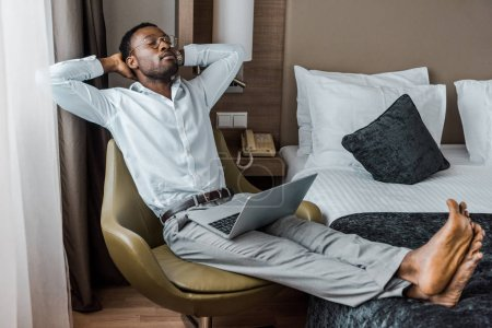 barefoot african american man with closed eyes relaxing in armchair with laptop in hotel room