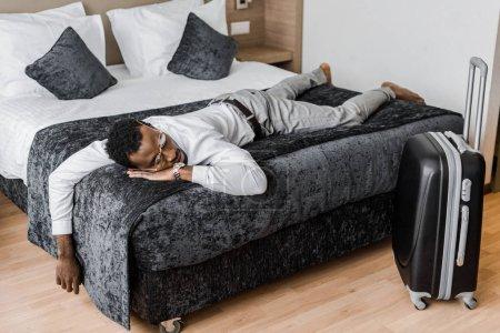 homme africain-américain fatigué en vêtements dormir sur le lit dans la chambre d'hôtel avec valise