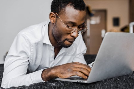 focused african american businessman in glasses working on laptop in hotel room