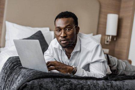 bel homme d'affaires afro-américains en lunettes de travail avec ordinateur portable sur lit d'hôtel