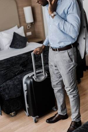 cropped view of african american businessman with travel bag in hotel room